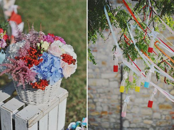 allestimento cerimonia all'aperto con cestini di fiori, bottigliette di vetro, girandole e nastri