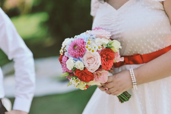 red, blue, pink bridal bouquet with hydrangeas, roses, dahlias, carnations, chamomile, garden roses and berries
