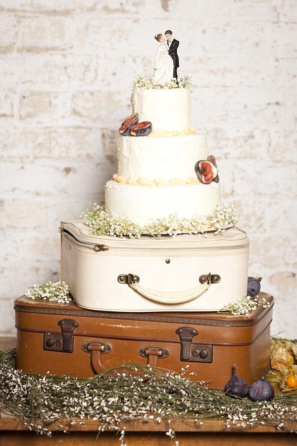 torta decorata con fichi e gypsophila su valigie vintage