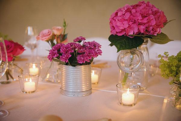 centrotavola con fiori fucsia in vasi di vetro e lattine