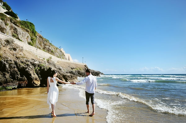 Couple walking on beach together holding hands
