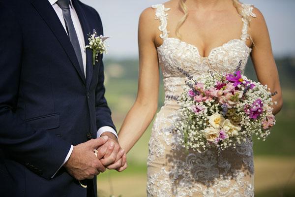 abito da sposa in pizzo e bouquet rosa e viola