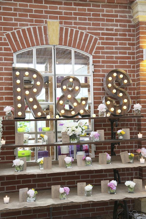 tableau de mariage con fiori, carta kraft e lettere luminose