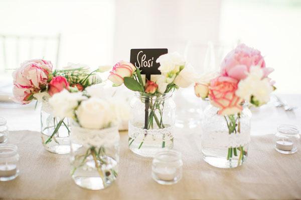 centrotavola con barattoli di vetro, pizzo e fiori