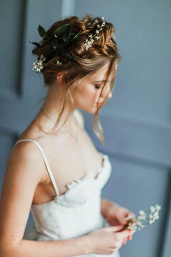 acconciatura raccolta sposa con fiori e foglie
