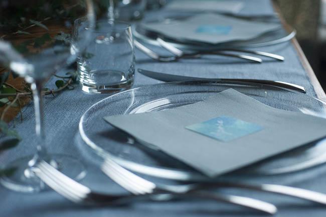 tavola con runner azzurro, edera e segnaposto acquerello