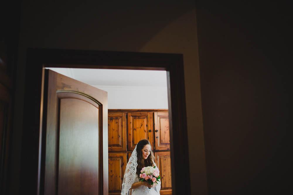 sposa con velo in pizzo e bouquet rosa