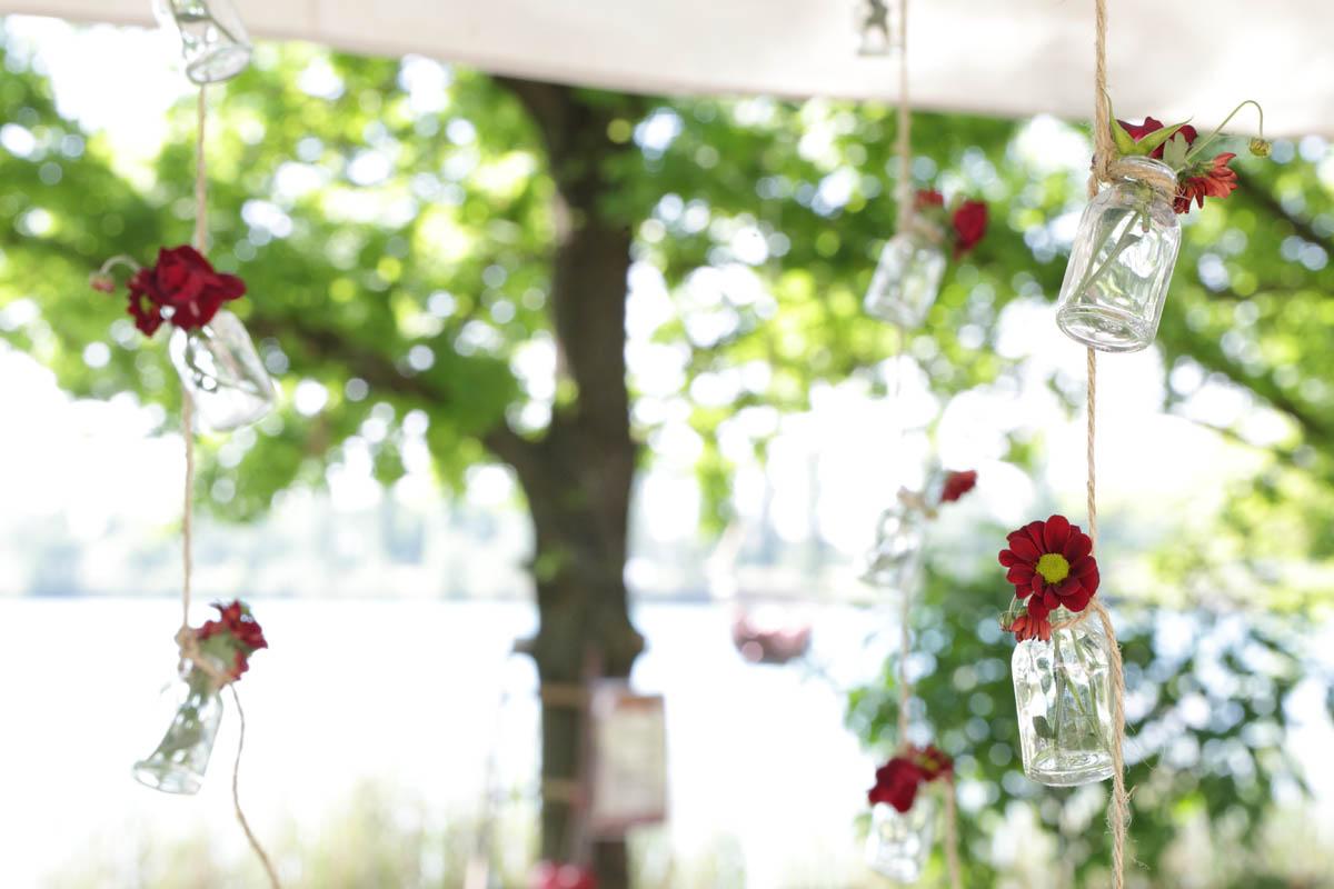 fiori rossi in bottiglie sospese