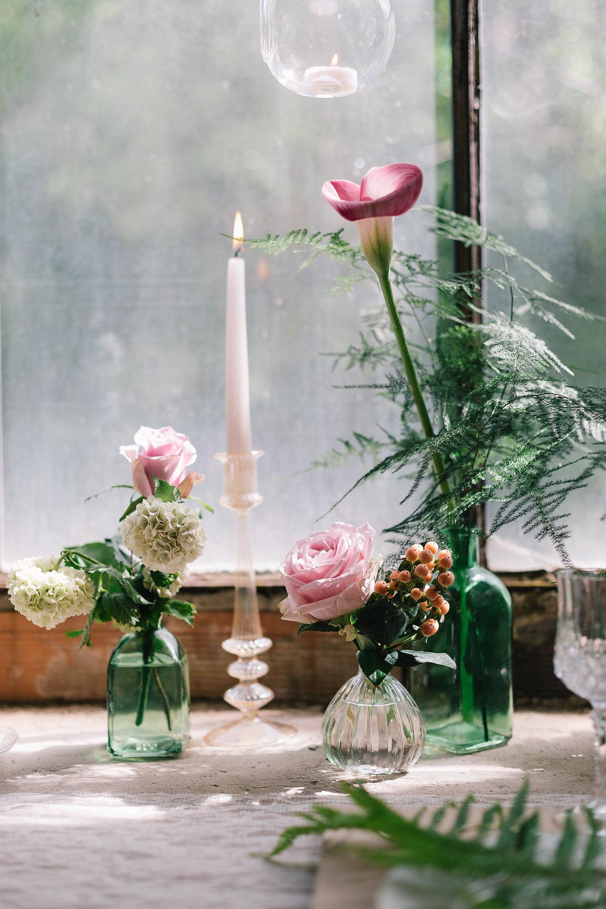 allestimento con fiori in bottiglie di vetro