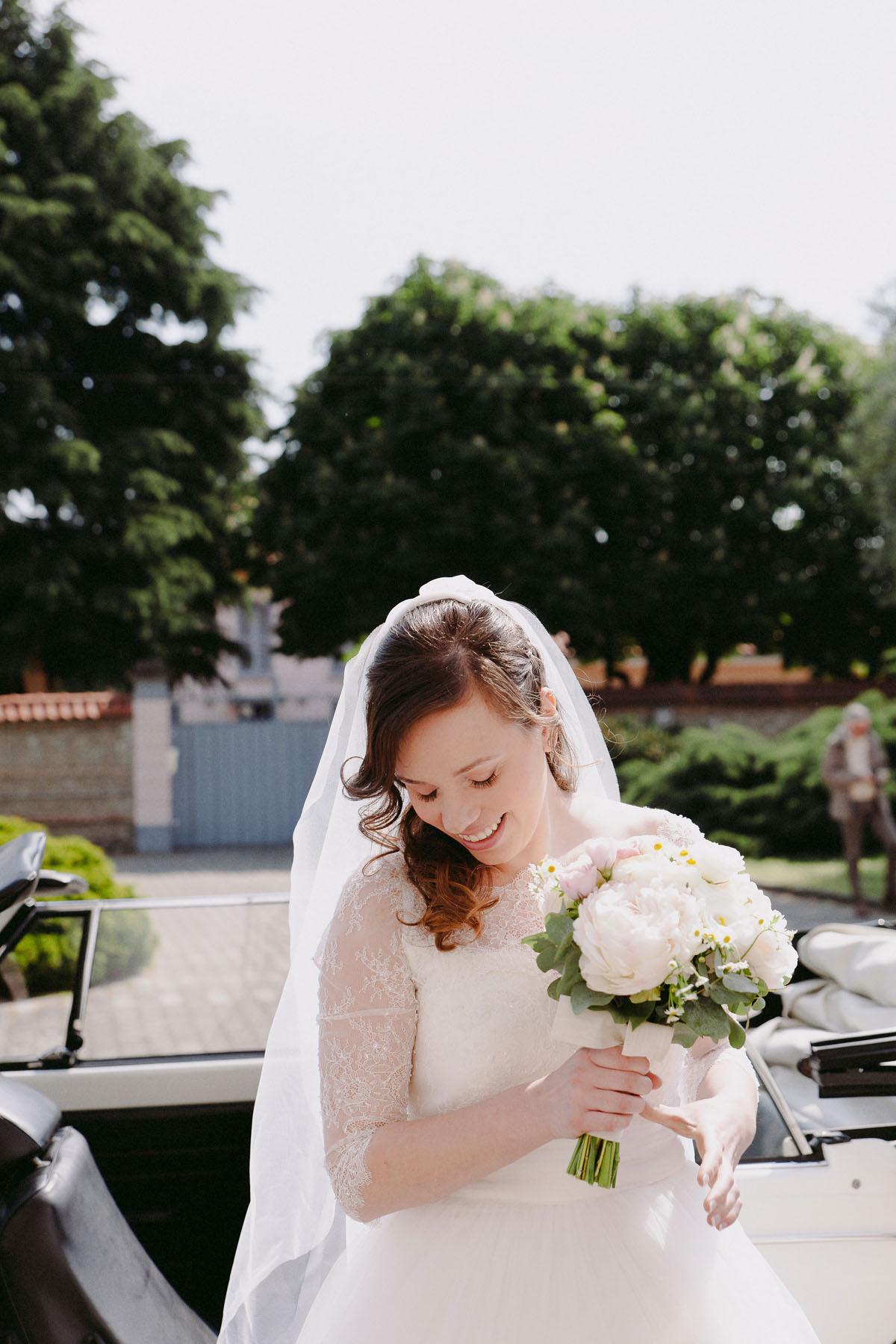 abito da sposa con maniche in pizzo e bouquet dai colori pastello