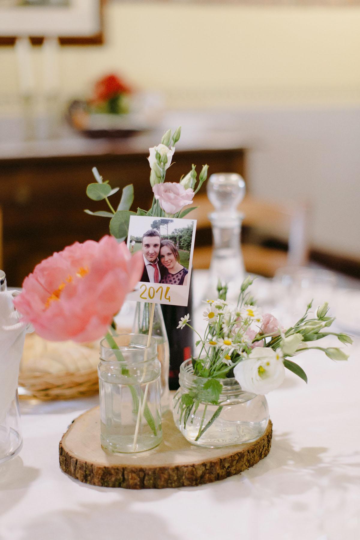 centrotavola matrimonio con vasetti di vetro, legno e polaroid