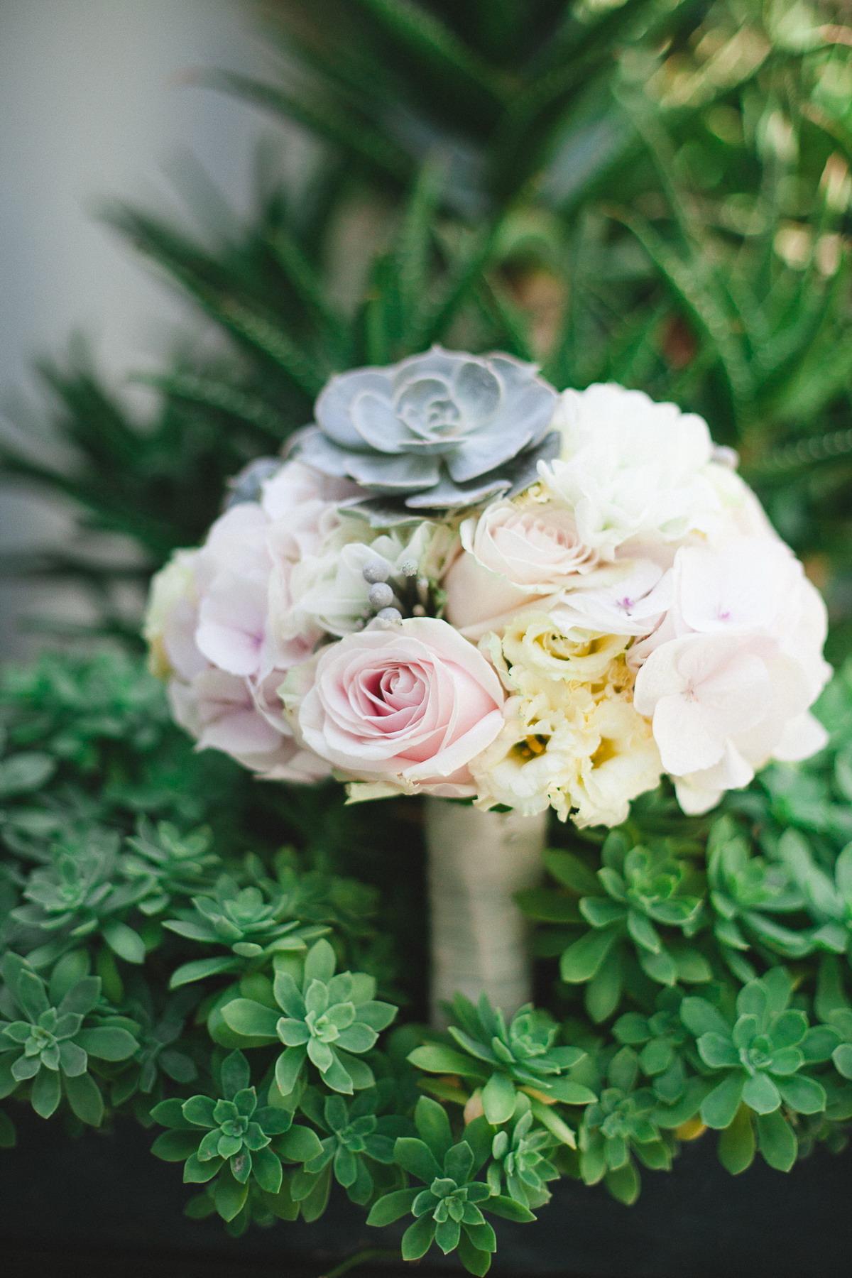 bouquet con rose, lisianthus, succulente e bacche silver brunia