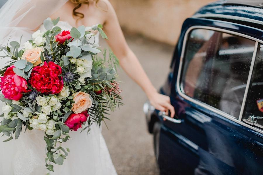 bouquet con peonie rosse, rose pesca, eryngium ed eucalipto