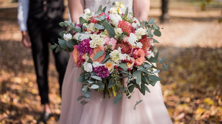 bouquet con rose, protea cynaroides, garofani, bacche ed eucalipto