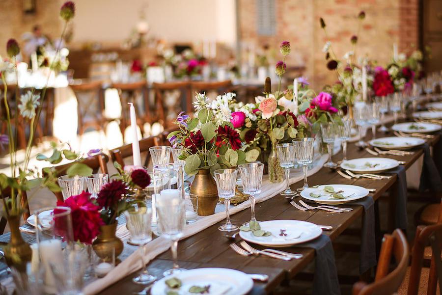 tavola in legno con fiori rossi e fucsia