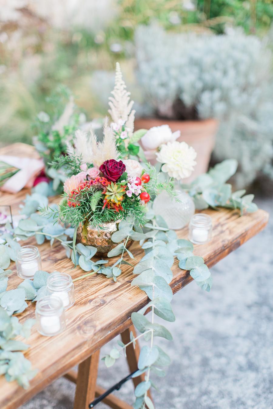 centrotavola con fiori bordeaux, rosa e foliage