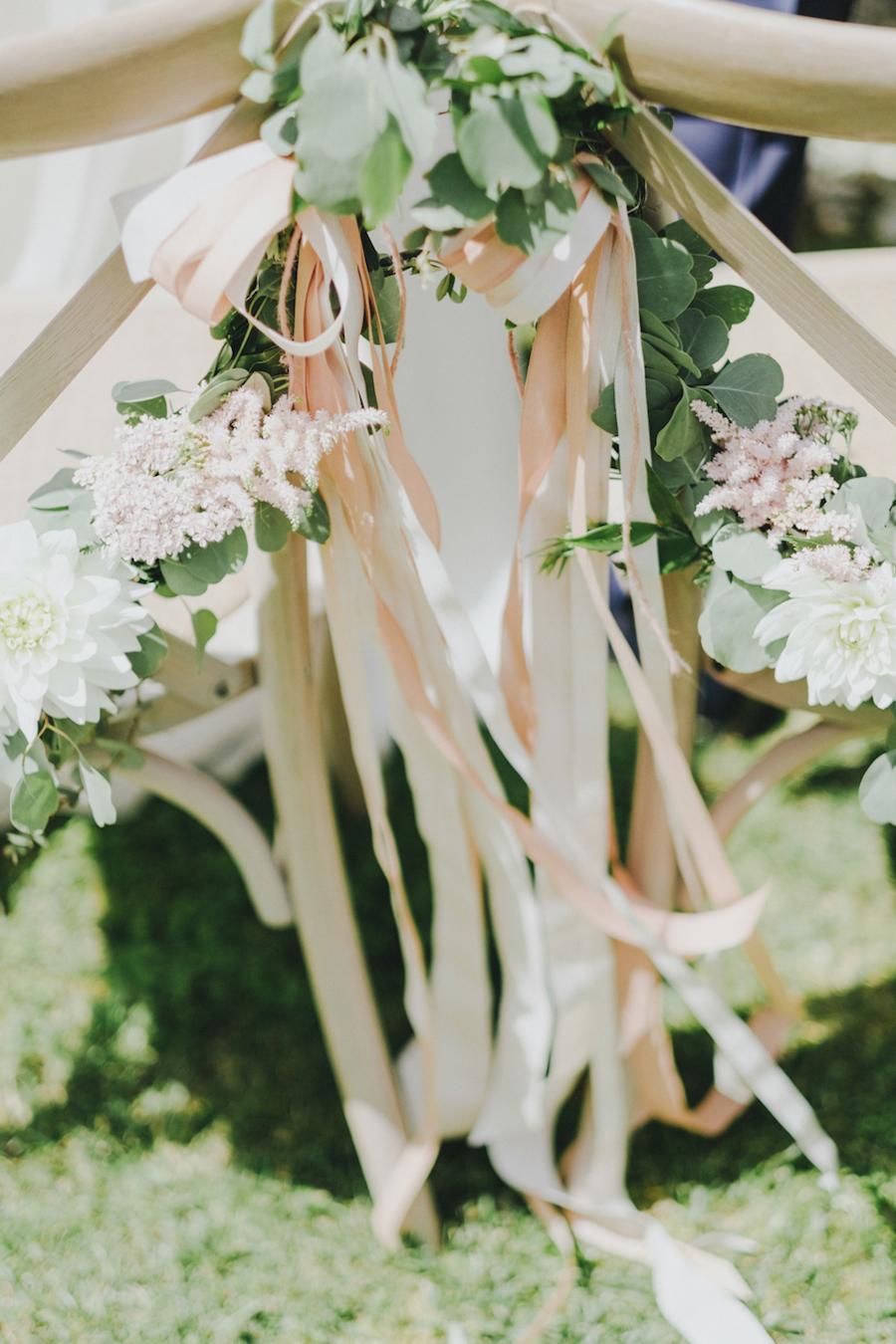 decorazione sedia con fiori, nastri ed eucalipto