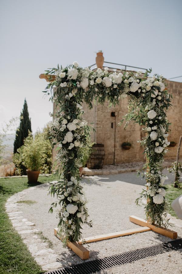 arco nuziale con fiori bianchi e foliage