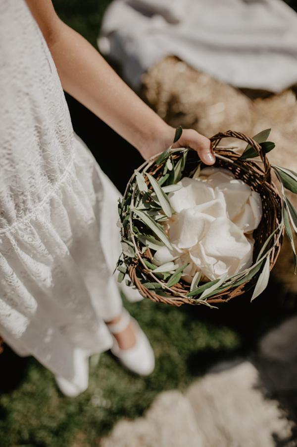damigella con cestino di petali e foglie d'ulivo