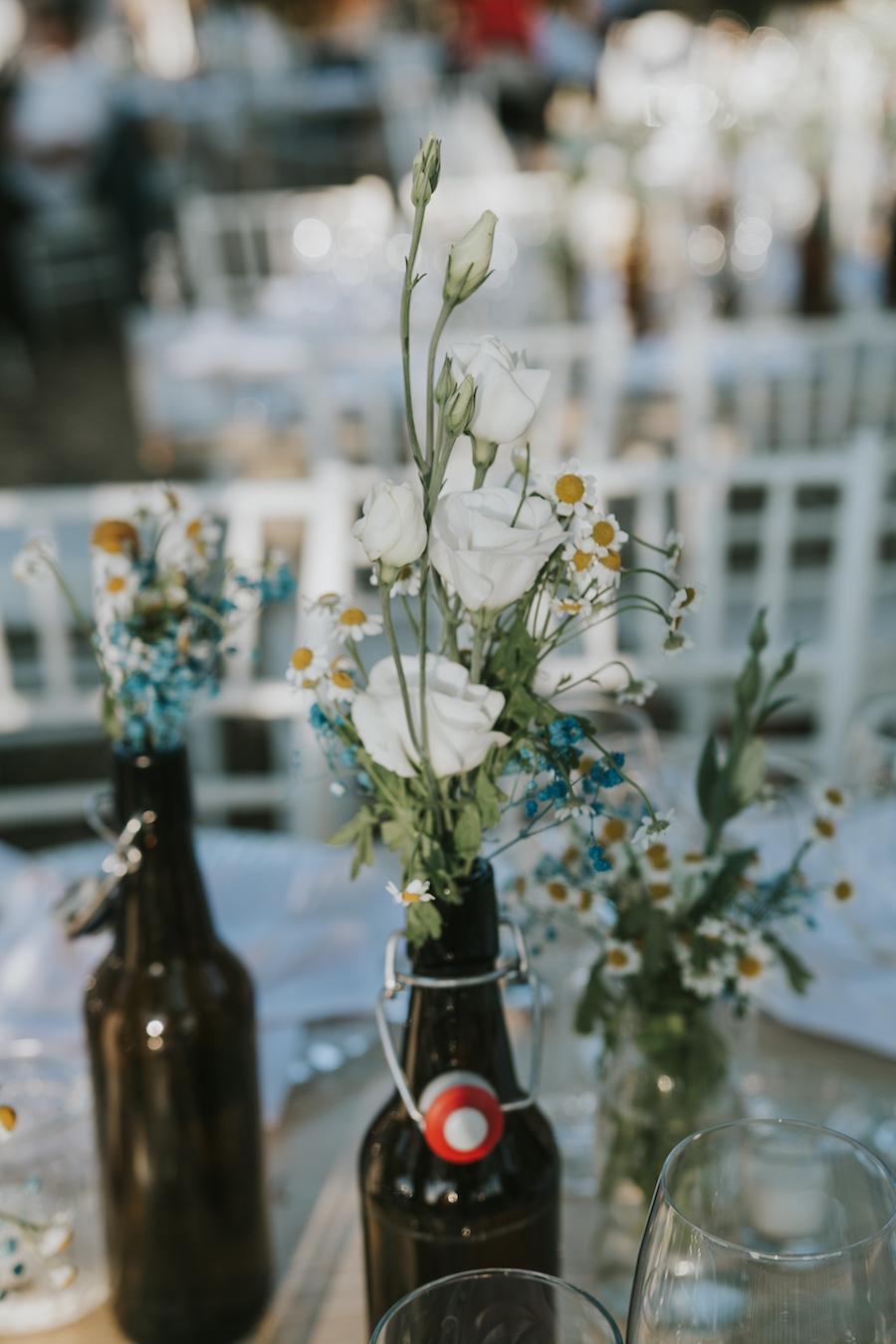 centrotavola con bottiglie e fiori di campo